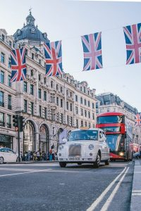 THis is aphoto of the city of London iwht Flags, Red Bus and Taxi driving along the street