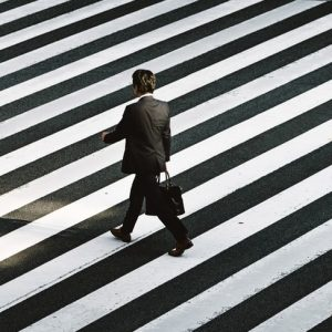 Photo in black and white of man walking on a zebra crossing