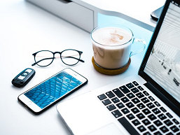 Photo of home office with coffee and PC and mobile phone